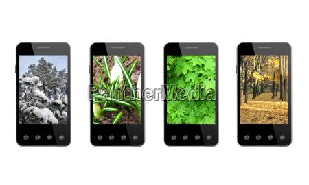 vier smartphones mit farbigen jahreszeitenbildern