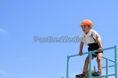 japanische kindergartenkind auf dem klettergeruest