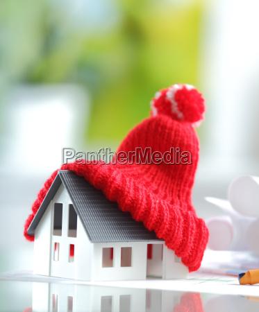 energiesparender roter gestrickter hut auf miniaturhaus