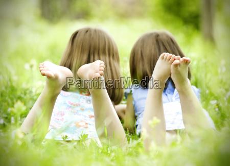 kinder liegen auf gruenem gras
