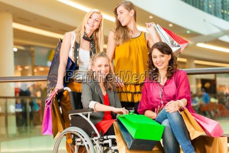 vier freundinnen beim shoppen in einer