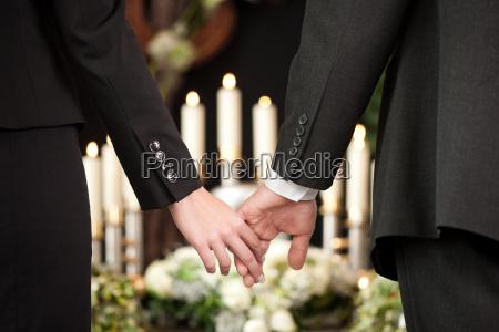 menschen bei der beerdigung troestlich einander