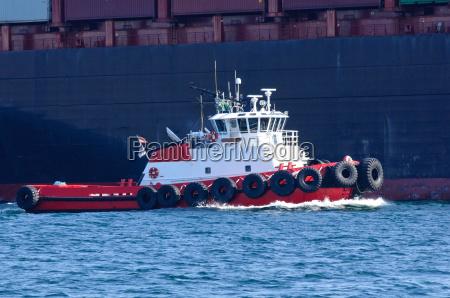 tug boat maneuvering to help cargo