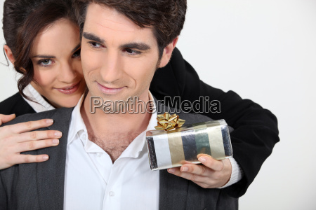 woman offering man surprise gift