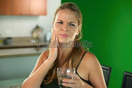 young woman with toothache drinking cold