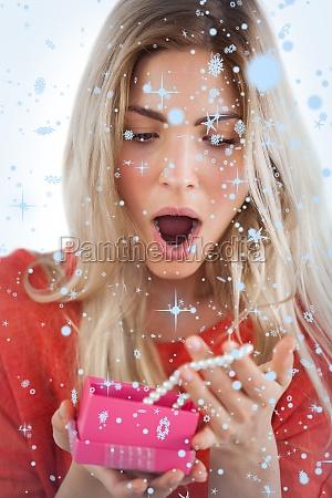 composite obraz zszokowanych kobieta odkrywa naszyjnik