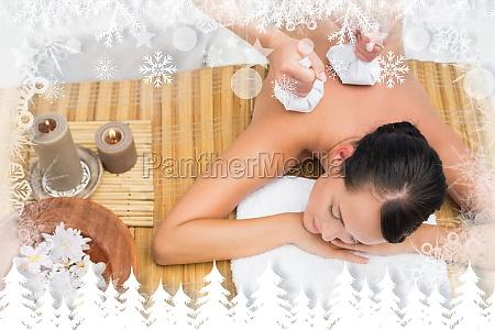 friedliche bruenette mit einer kraeuterkompresse massage