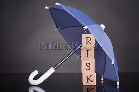 risiko wooden blocks unter regenschirm