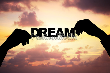 silhouette businessmans hands holding dream during