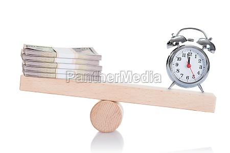 alarmuhr und dollar bundles balancieren auf