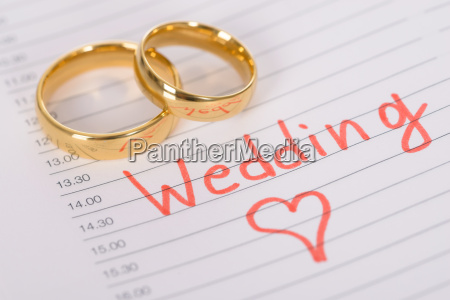 wedding rings on paper with time