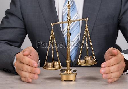 geschaeftsmann schutz gerechtigkeit waage mit muenzen