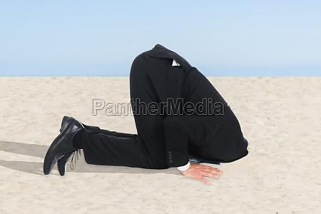 geschaeftsmann versteckt seinen kopf in sand