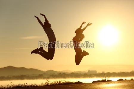 fitness paar springen gluecklich bei sonnenuntergang