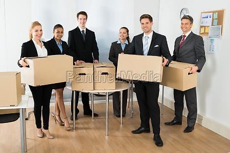 mitarbeiter in office holding cardboard boxen