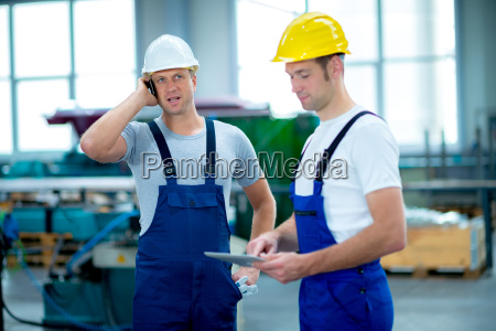 two man together in factory with