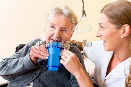pflegerin gibt alter frau tee zum