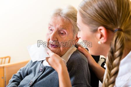 altenpflegerin wischt alter frau den mund