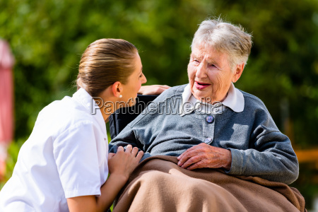 nurse holding hands with senior woman