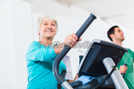 senior on eliptical trainer makes sport