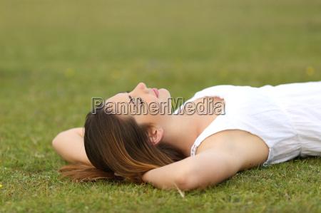entspannte frau die auf dem gras
