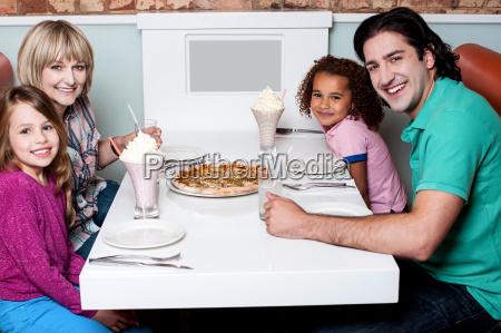 family of four posing to camera