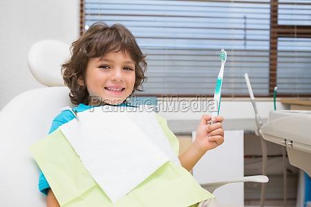 kleiner junge im zahnarztstuhl der toothrbrush