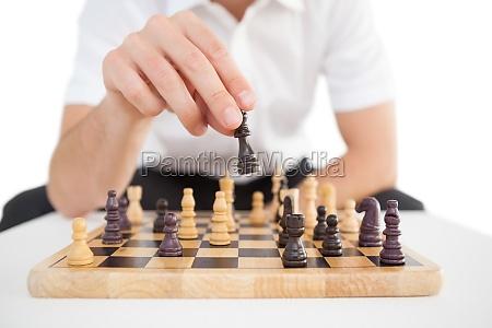 fokussierte geschaeftsmann spielt schach solo