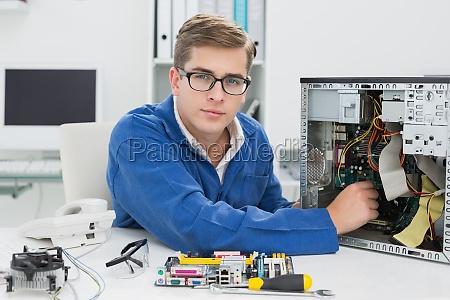junger techniker arbeitet am kaputten computer