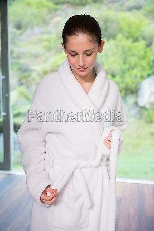 junge frau traegt einen bademantel