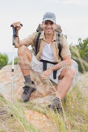 wandern mann sitzt auf alpinem gelaende