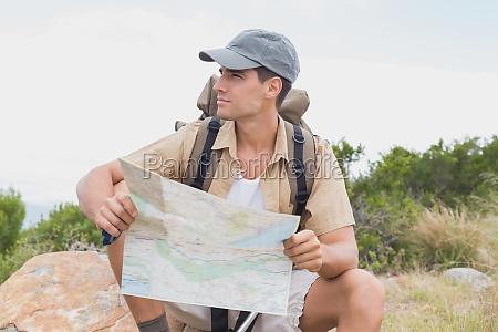 wandern mann mit karte sitzt auf