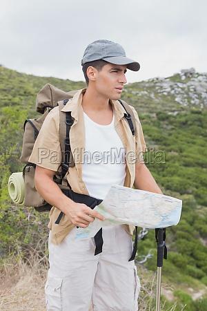 wandern mann haelt karte auf alpinem