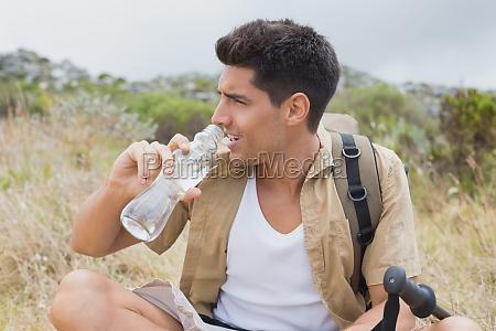 wandern mann trinkwasser auf alpinem gelaende