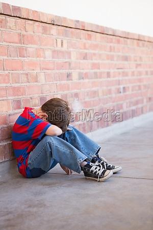 trauriger schueler allein im flur sitzen