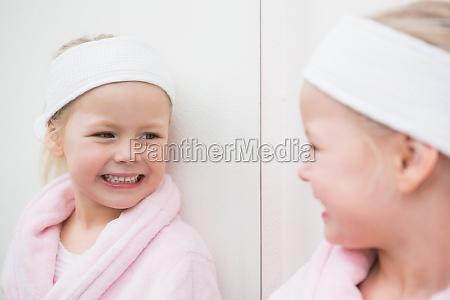 nettes kleines maedchen das im spiegel