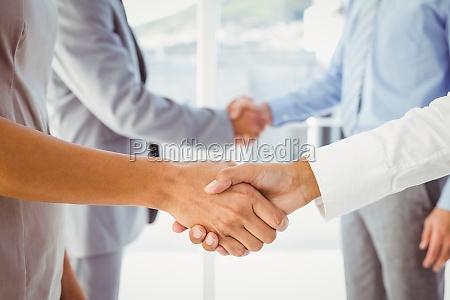 zwei mitangestellte schuetteln die haende