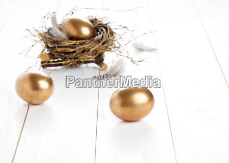 goldene ei auf weissem holzuntergrund