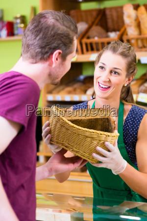 baeckerei verkaeuferin bietet kunden brot an