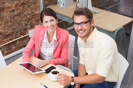 geschaeftskollegen mit kaffeetasse und digitalem tablet
