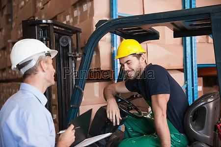 lagerleiter im gespraech mit staplerfahrer