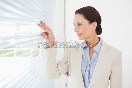 geschaeftsfrau schaut die jalousien aus