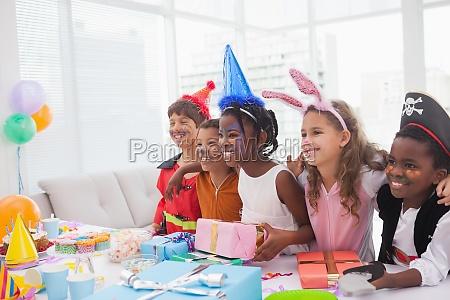 glueckliche kinder an der abendkleidgeburtstagsfeier