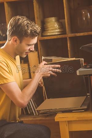 junger mann der seine vinylsammlung betrachtet