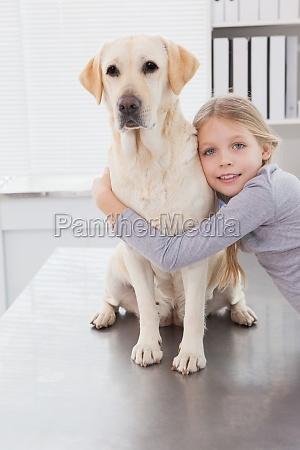 blonde inhaber umarmt ihren niedlichen hund