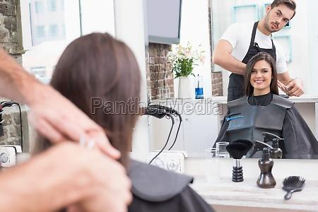 huebscher brunette der ihre haare schneiden