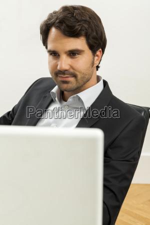 junger erfolgreicher geschaeftsmann mit schwarzem anzug