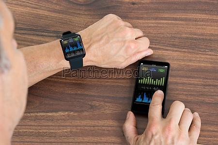 mann mit smartwatch und handy angezeigt