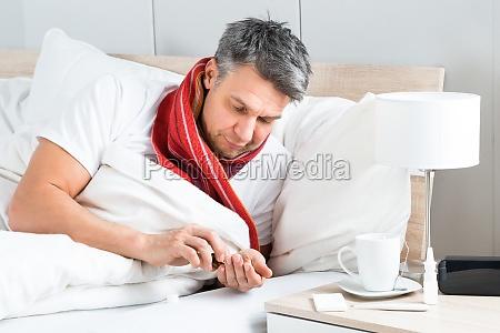 sick man having medicine in bed
