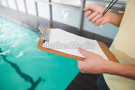 schwimmen trainer halten stoppuhr und zwischenablage
